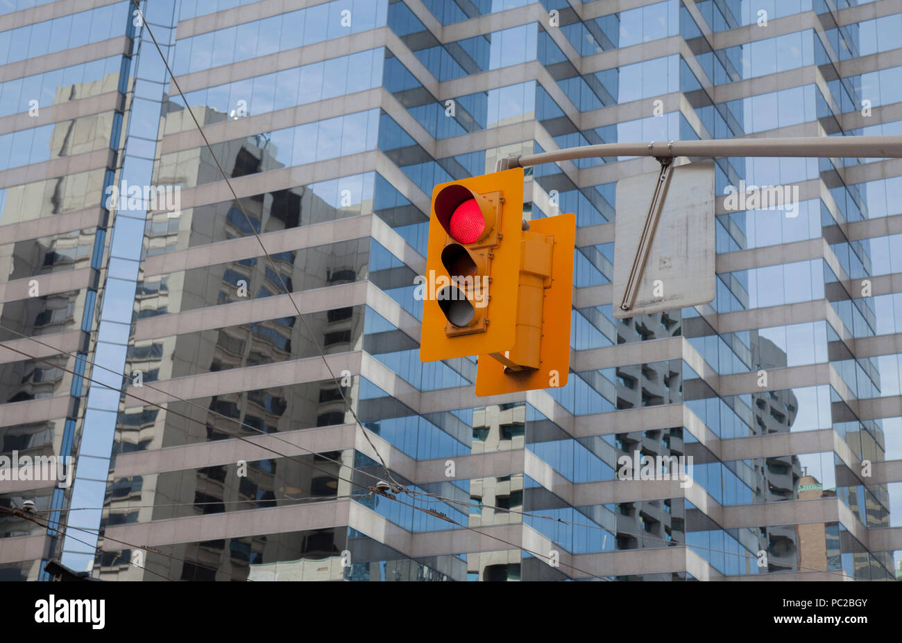 Red color traffic light with modern glass buildings in the background in the city centre of Toronto, Canada Stock Photo