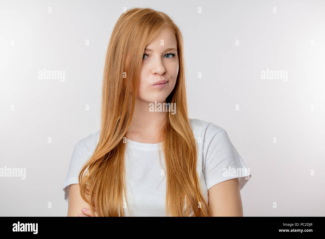 a beautiful redheaded girl is frowning as she is disagreeing with something . woman feels displeased of bad news. discontent and dissatisfaction conce - Stock Image