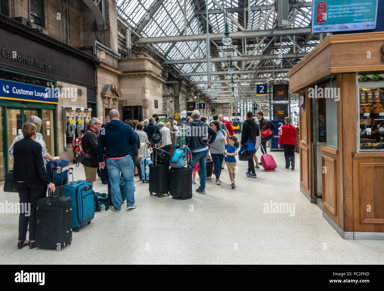 Passengers queueing to board a Virgin train from Platform 1 in Glasgow Central Station. Train travel, rolling luggage, standing, waiting in line Stock Photo