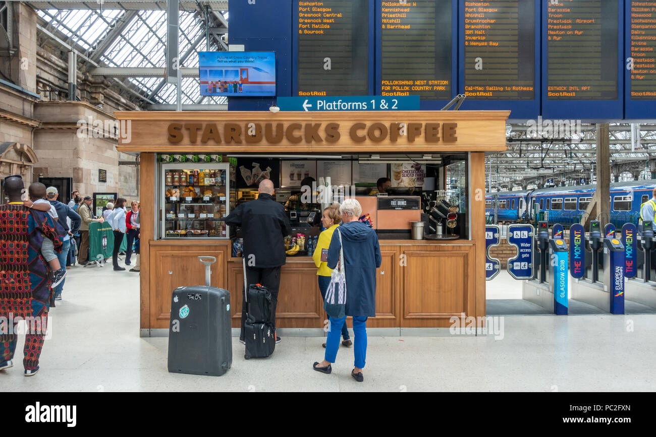 Baristas and customers at the Starbucks outlet in Glasgow Central Station. Passengers queuing for train. Departures board. Ticket barriers. - Stock Image