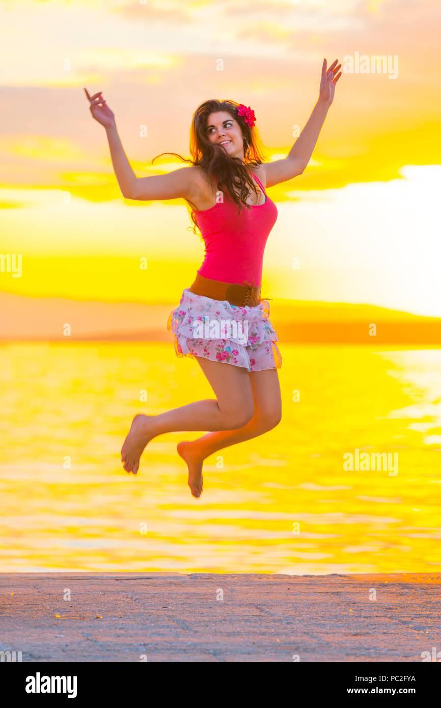 Jumping before sunset sunshine bright sea - Stock Image