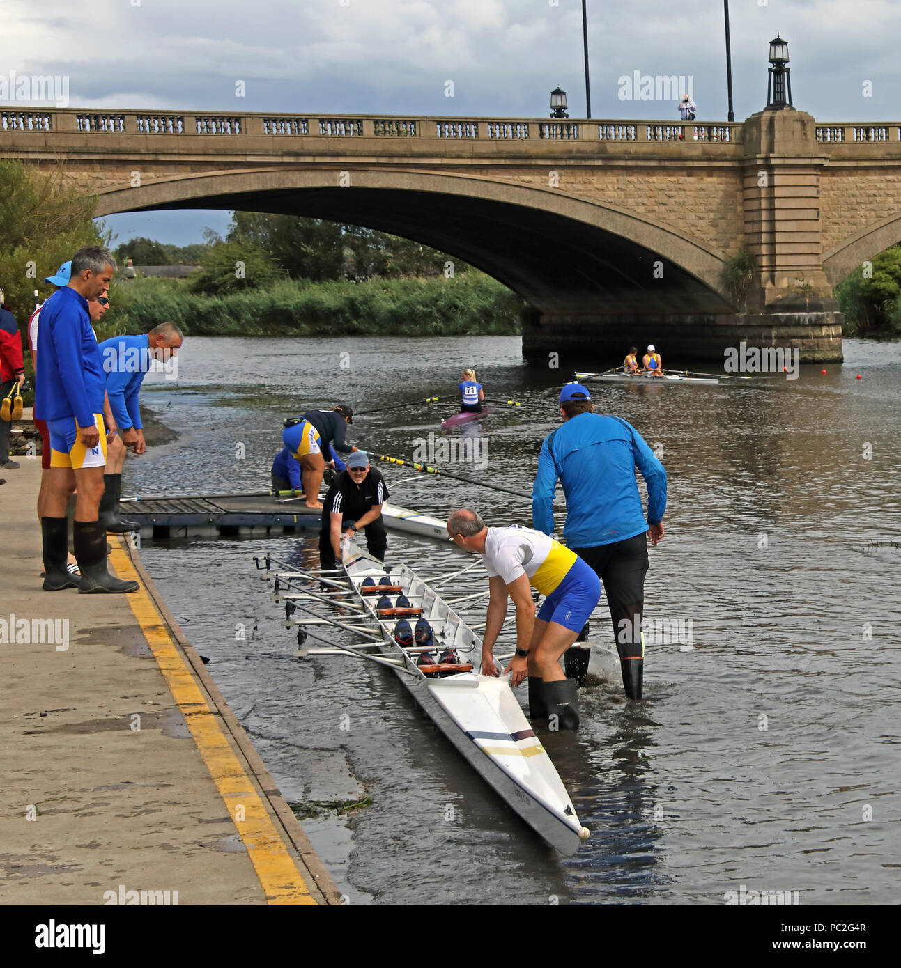 Launching a quad, at Warrington Rowing Club 2018 Summer regatta, Howley lane, Mersey River, Cheshire, North West England, UK - Stock Image