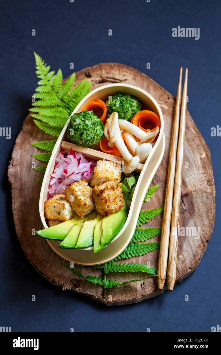 Japanese bento box lunch withg mushrooms, onigiri and tofu - Stock Image