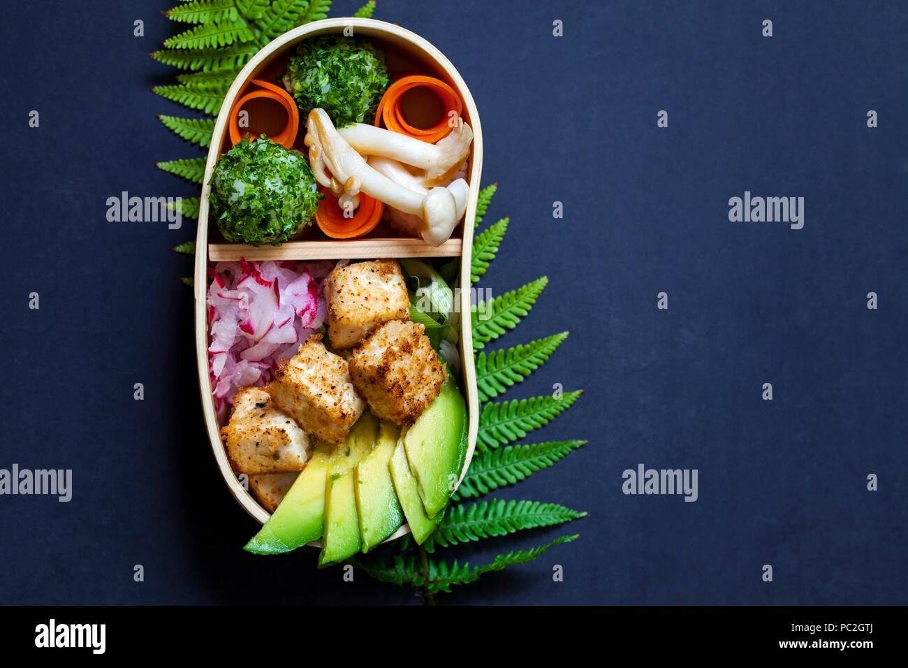 Japanese bento box lunch withg mushrooms, onigiri and tofu - Stock Image