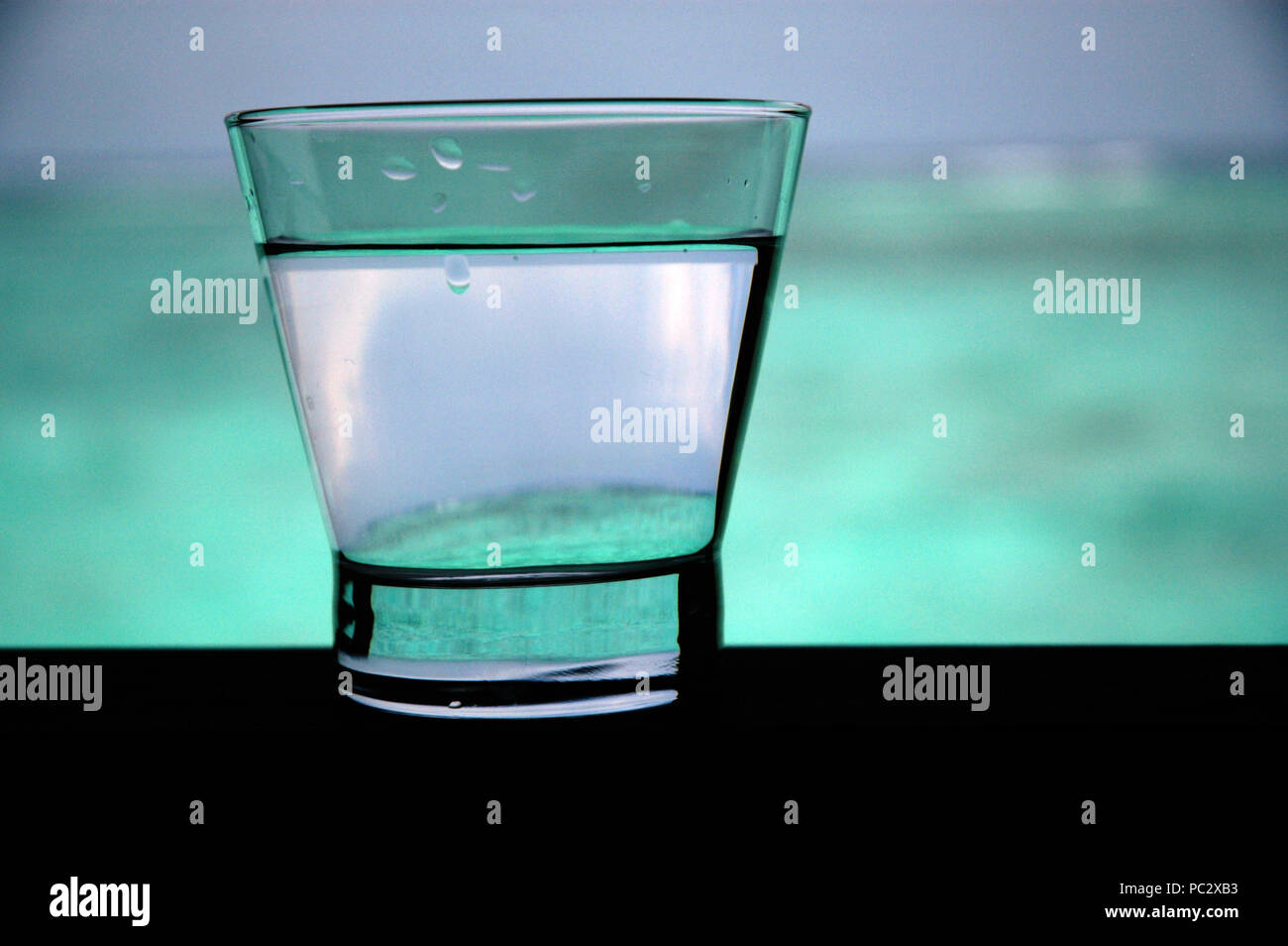 Still life of water filled glass at dusk, The Maldives, Republic of Maldives - Stock Image