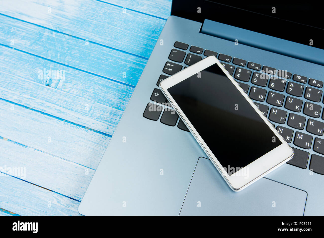 Gradient Blue Brand New Laptop With Balck Keyboard Closeup With  White Empty Screen Smartphone On Blue Wood Surface Studio Shot - Stock Image