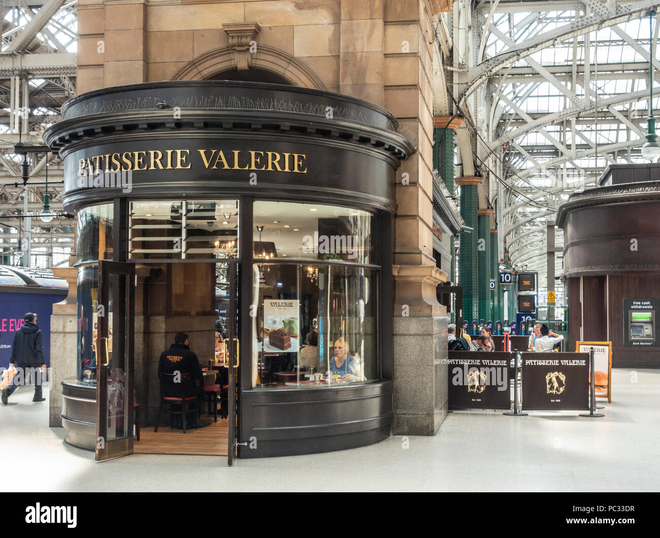 Exterior of, and customers in, the branch of Patisserie Valerie pastry cafe in Glasgow Central Station. - Stock Image