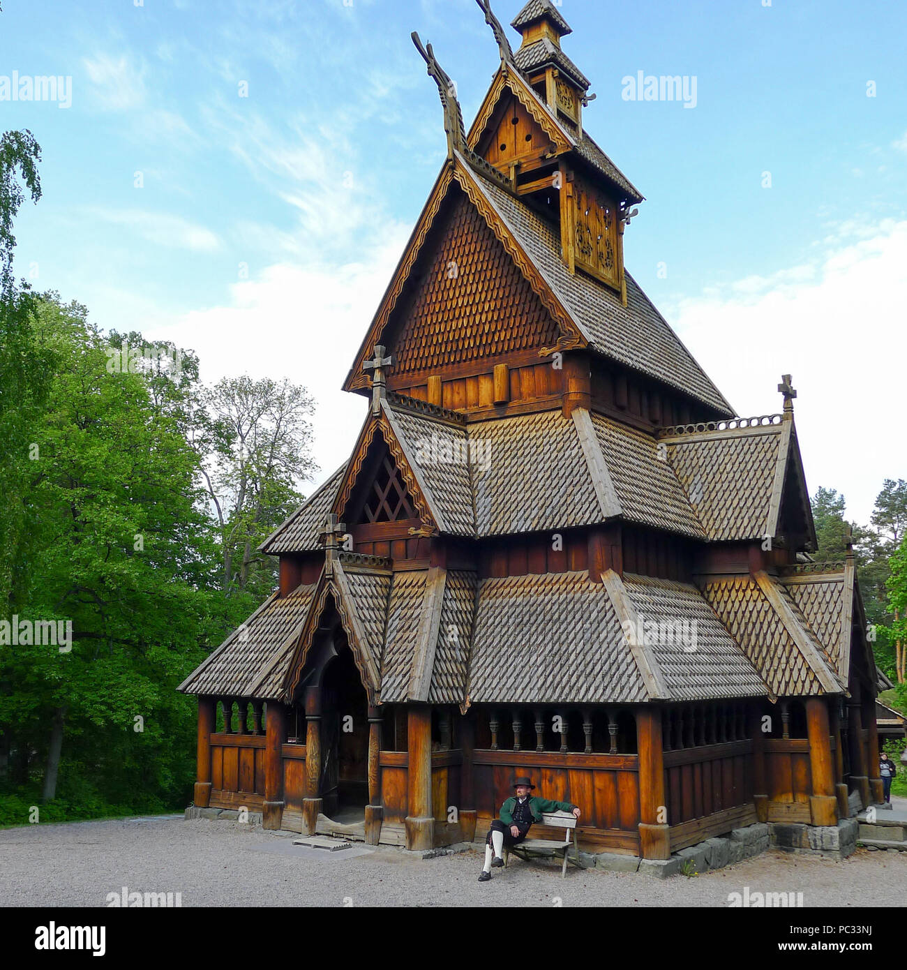 Man in traditional costume sitting in front of the Stave Church from Gol at the Norsk Folkemuseum in Oslo, Norway. - Stock Image