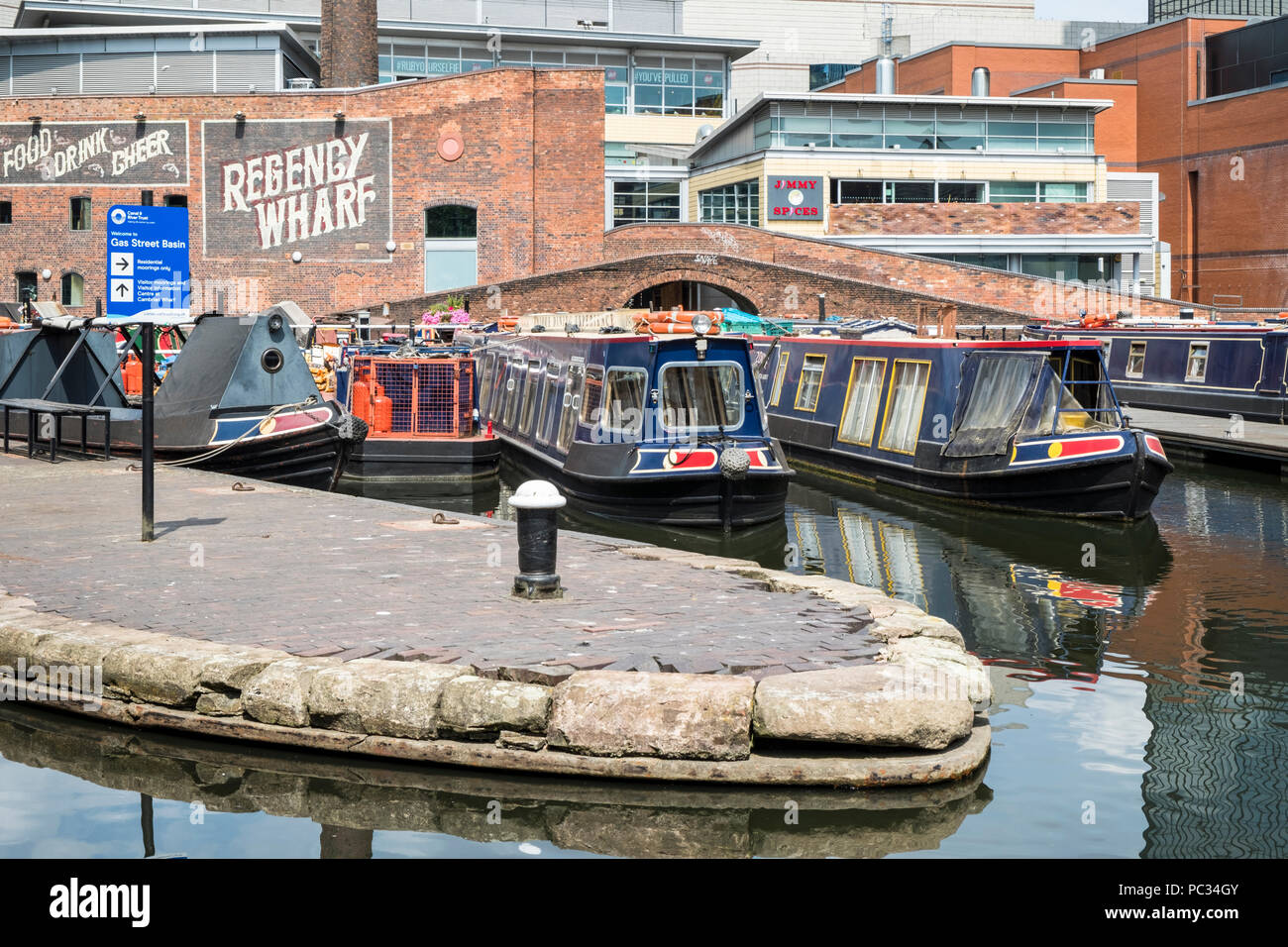 Moored narrowboats at Regency Wharf, Gas Street Basin in Birmingham city centre, England, UK. - Stock Image