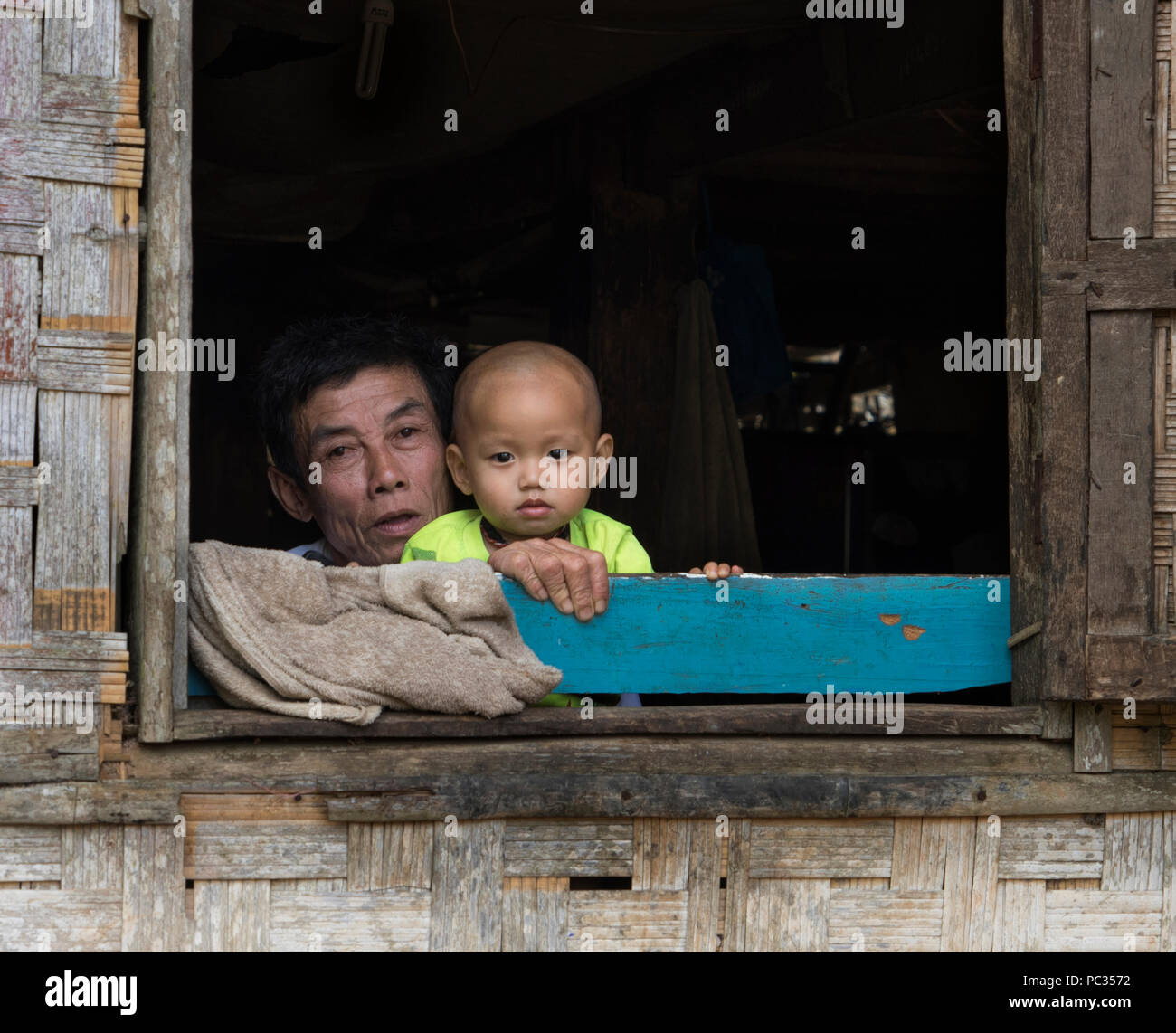 Father and son at the window in Northern Laos ethnic minorities village - Stock Image