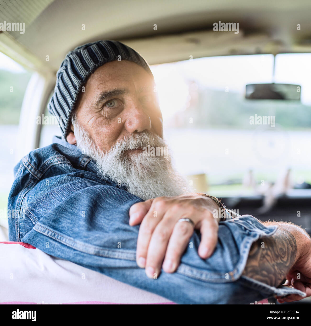 Portrait of an old hipster sitting in a van looking at camera - Stock Image