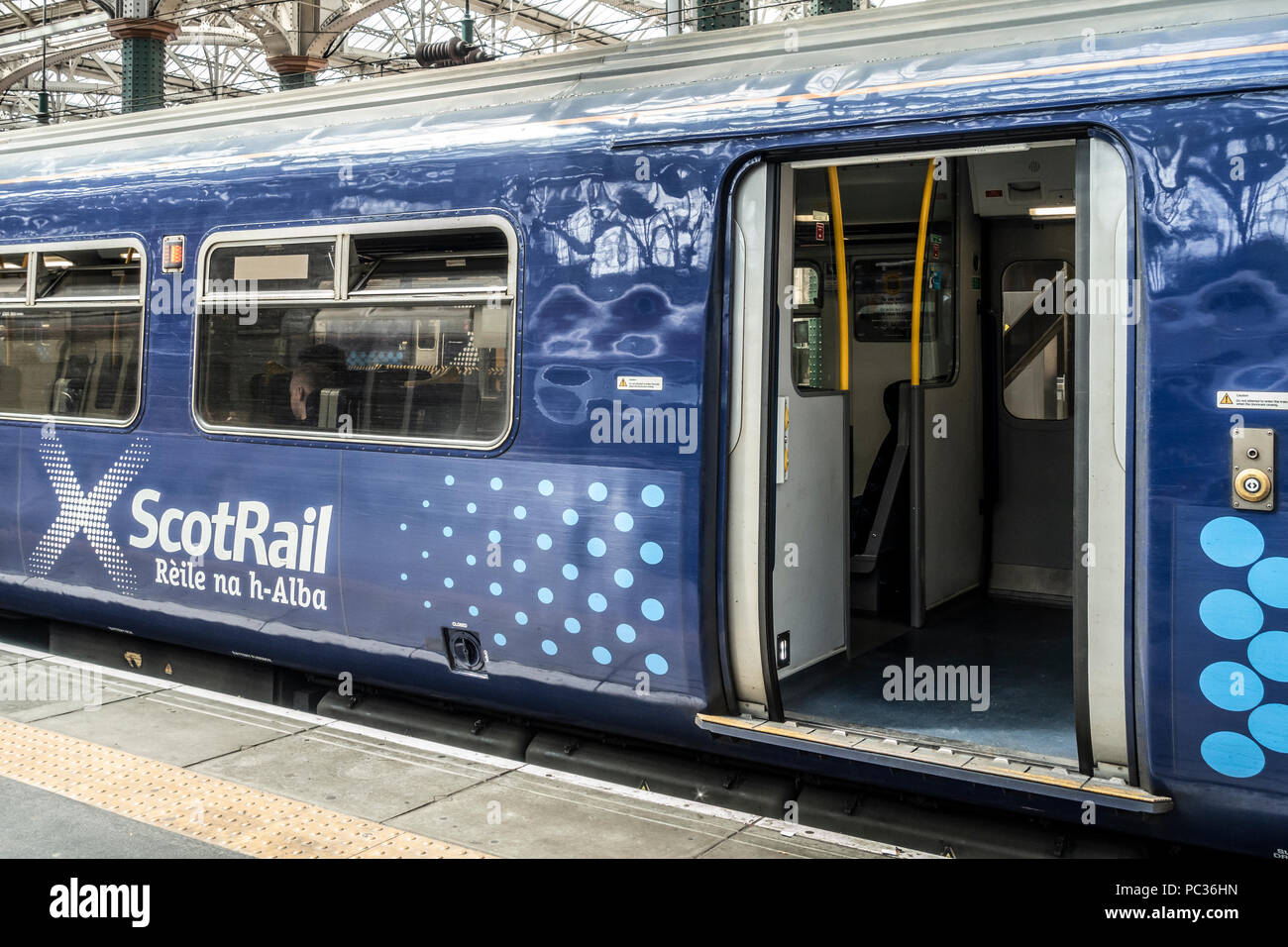 Scotrail train carriage with Saltire logo / branding, with open door. Passenger visible through window. Glasgow Central Station, - Stock Image