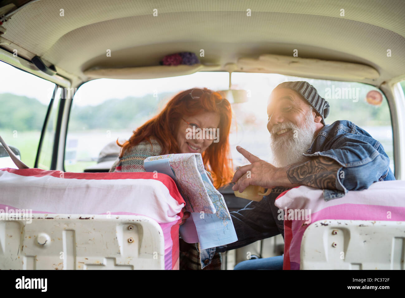 An old hipster couple sitting in a camper van, drinking coffee and looking at a road map. he is tattooed and he wears a white beard, she had red hair - Stock Image