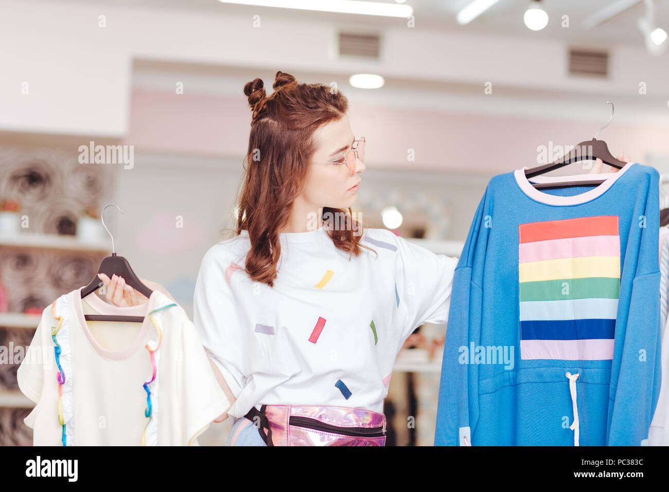 Two items. Shopaholic wearing bright pink waist bag choosing between two items while hesitating a little bit - Stock Image