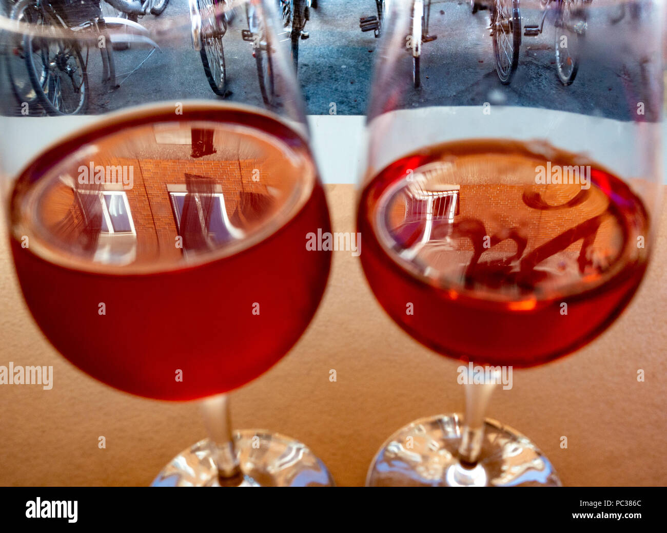 Reflections from windows in rose wine in glasses, bicycles in background - Stock Image