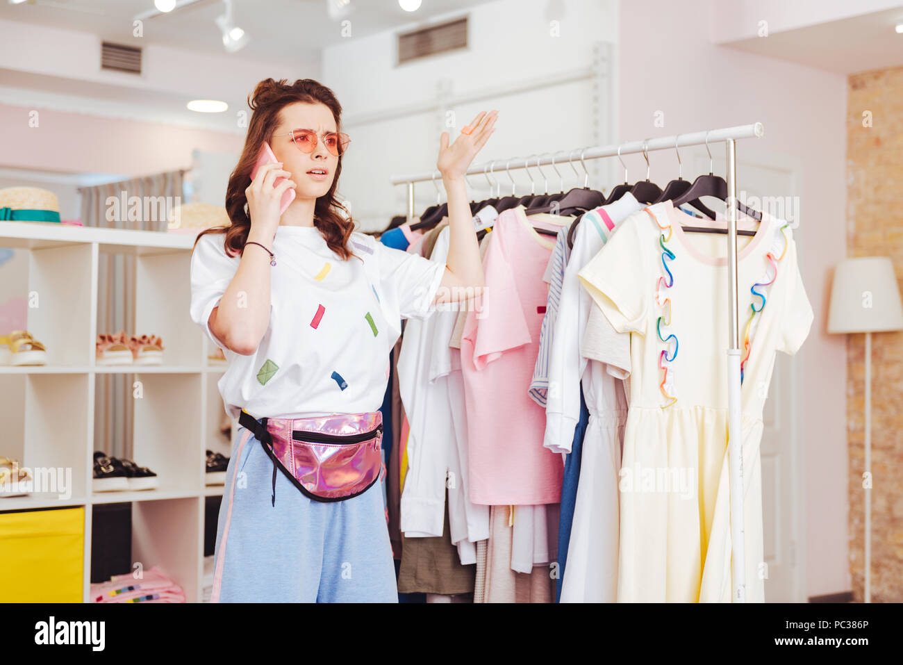 Arguing with man. Emotional woman arguing with her man while speaking on the phone standing in showroom - Stock Image