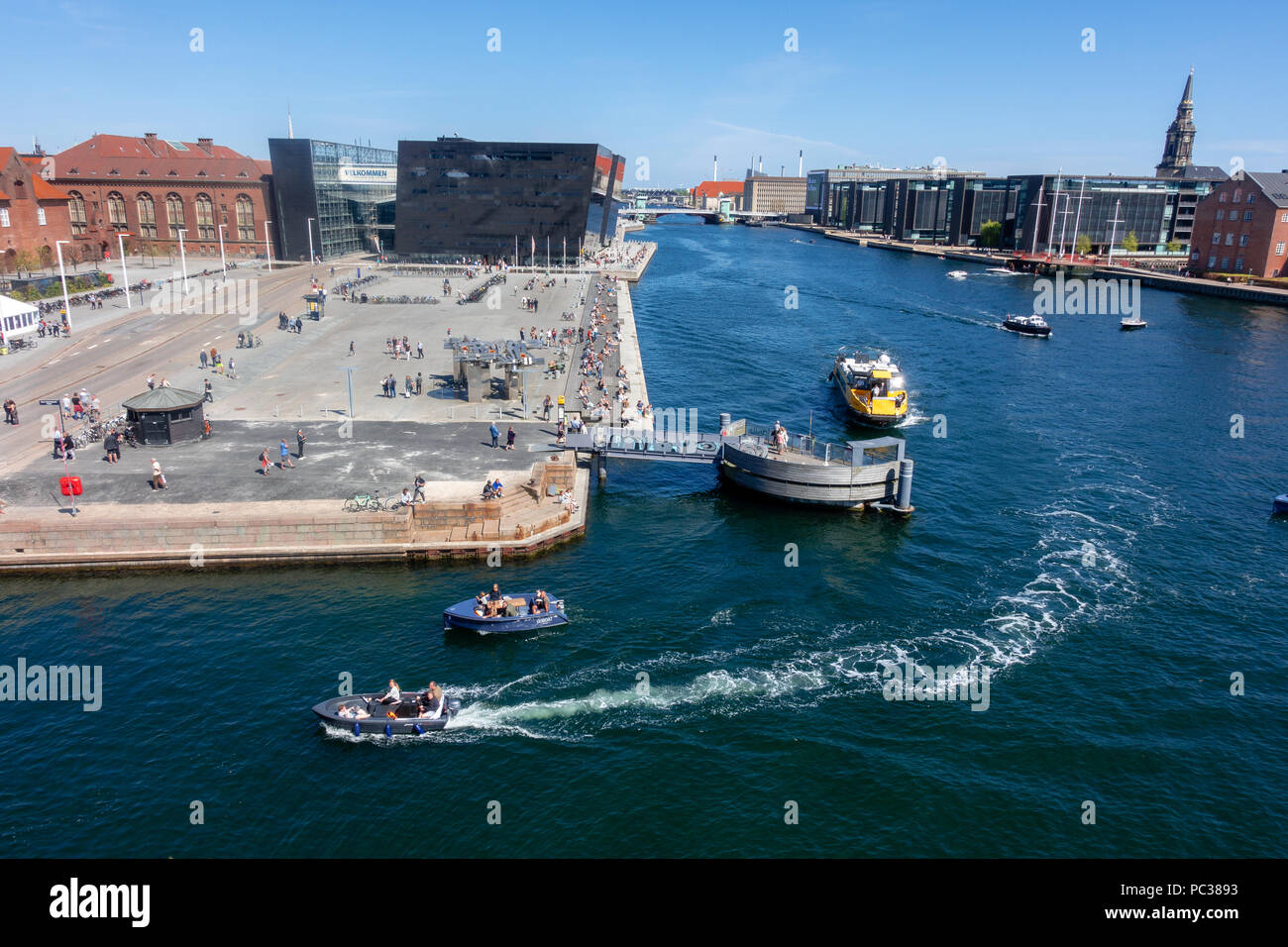 Copenhagen waterfront with The Black Diamond and Soren Kierkegaards Square, yellow water bus and boats, seen from DAC's terrace in the Blox building - Stock Image