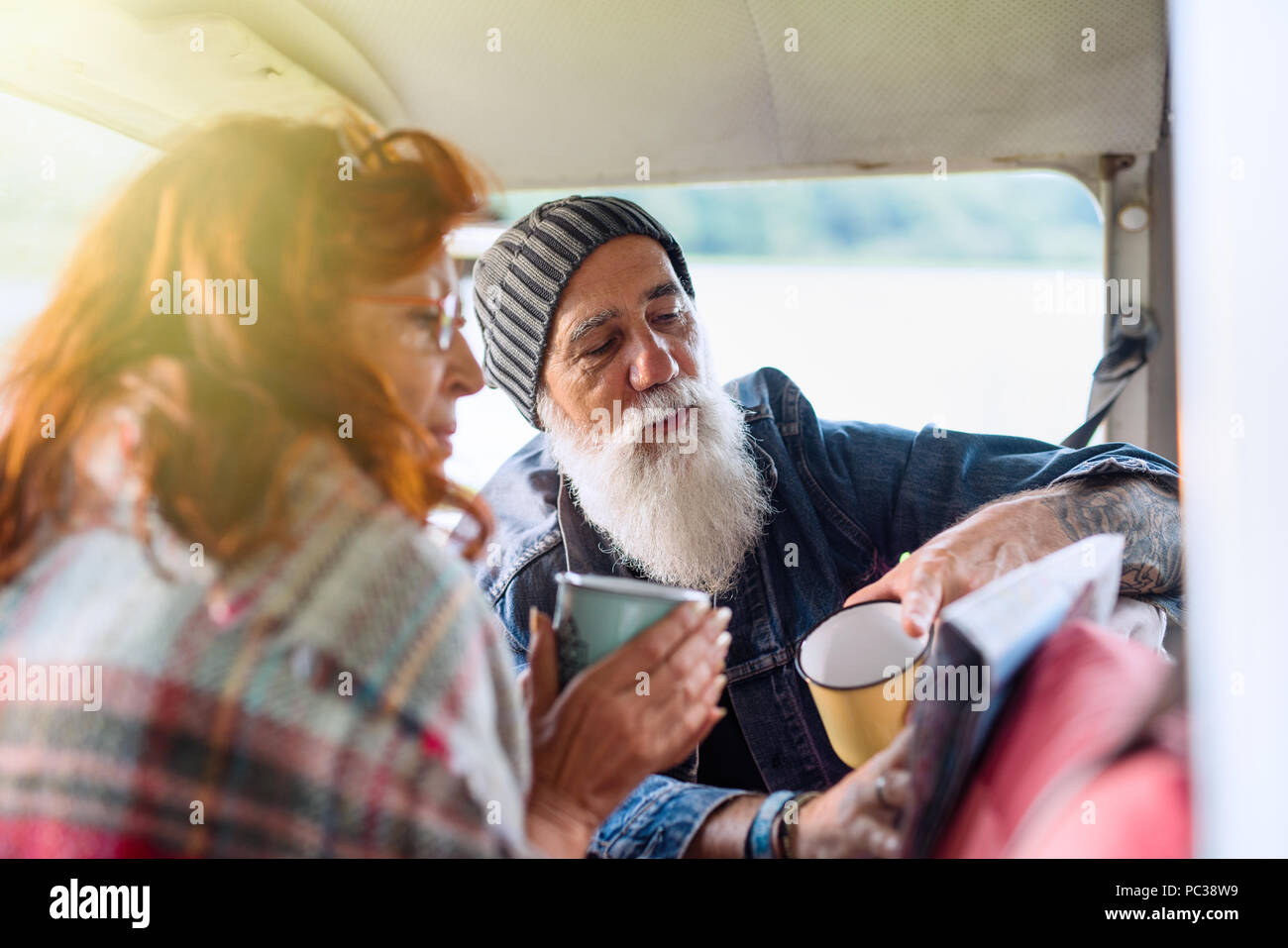 Old hipster couple sitting in a van and looking at a road map  - Stock Image