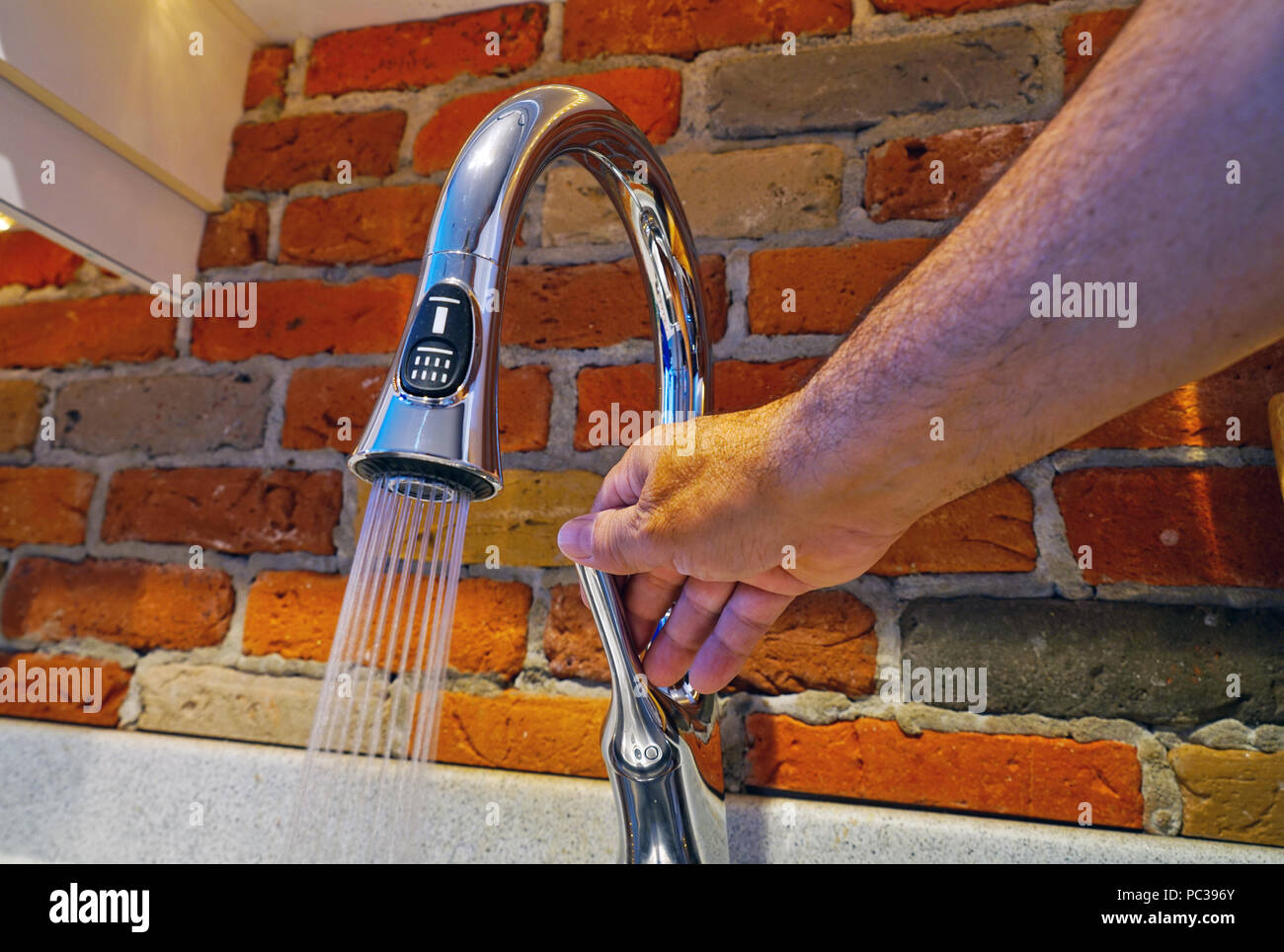 Montreal, Canada, July 31, 2018.Hand adjusting water flow out of kitchen faucet.Credit Mario Beauregard/Alamy Live News - Stock Image