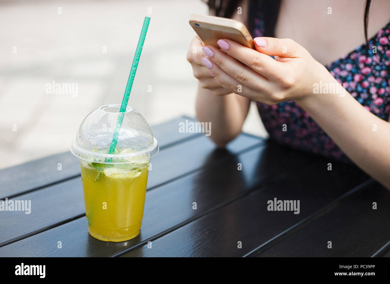 Young girl drinks refreshing cold mojito cocktail while using smartphone device in hands. Always connected person uses mobile phone in green park at d - Stock Image