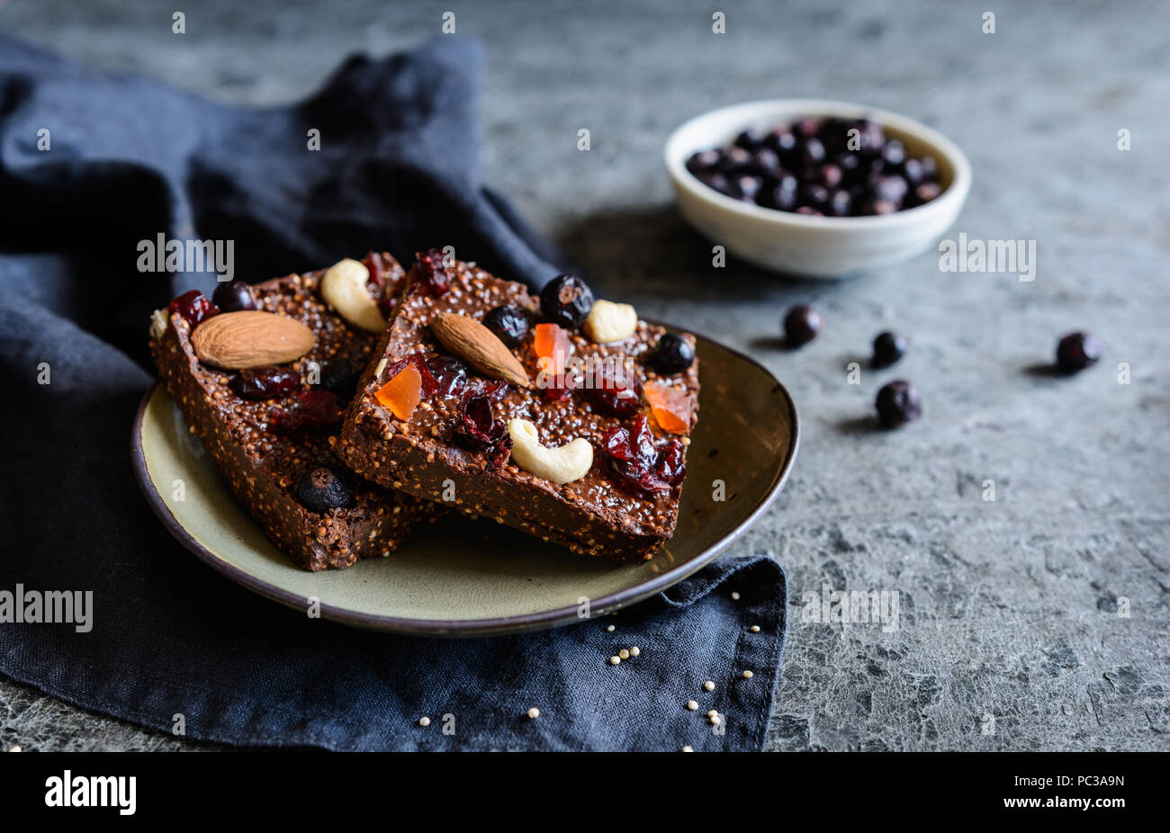 No bake chocolate puffed quinoa bars with freeze dried black currant, candied papaya, cashew nuts, almonds and cranberries Stock Photo