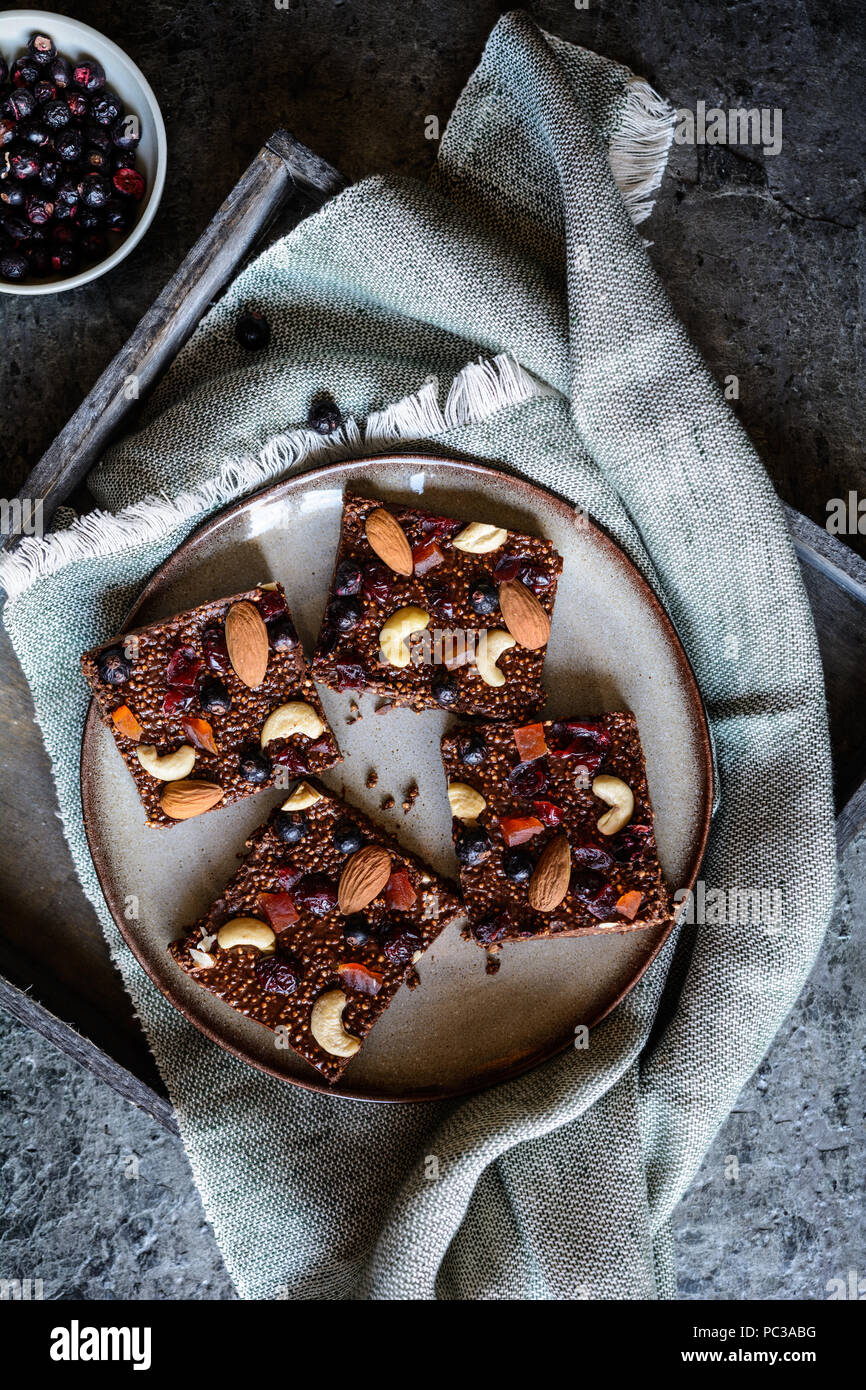No bake chocolate puffed quinoa bars with freeze dried black currant, candied papaya, cashew nuts, almonds and cranberries - Stock Image