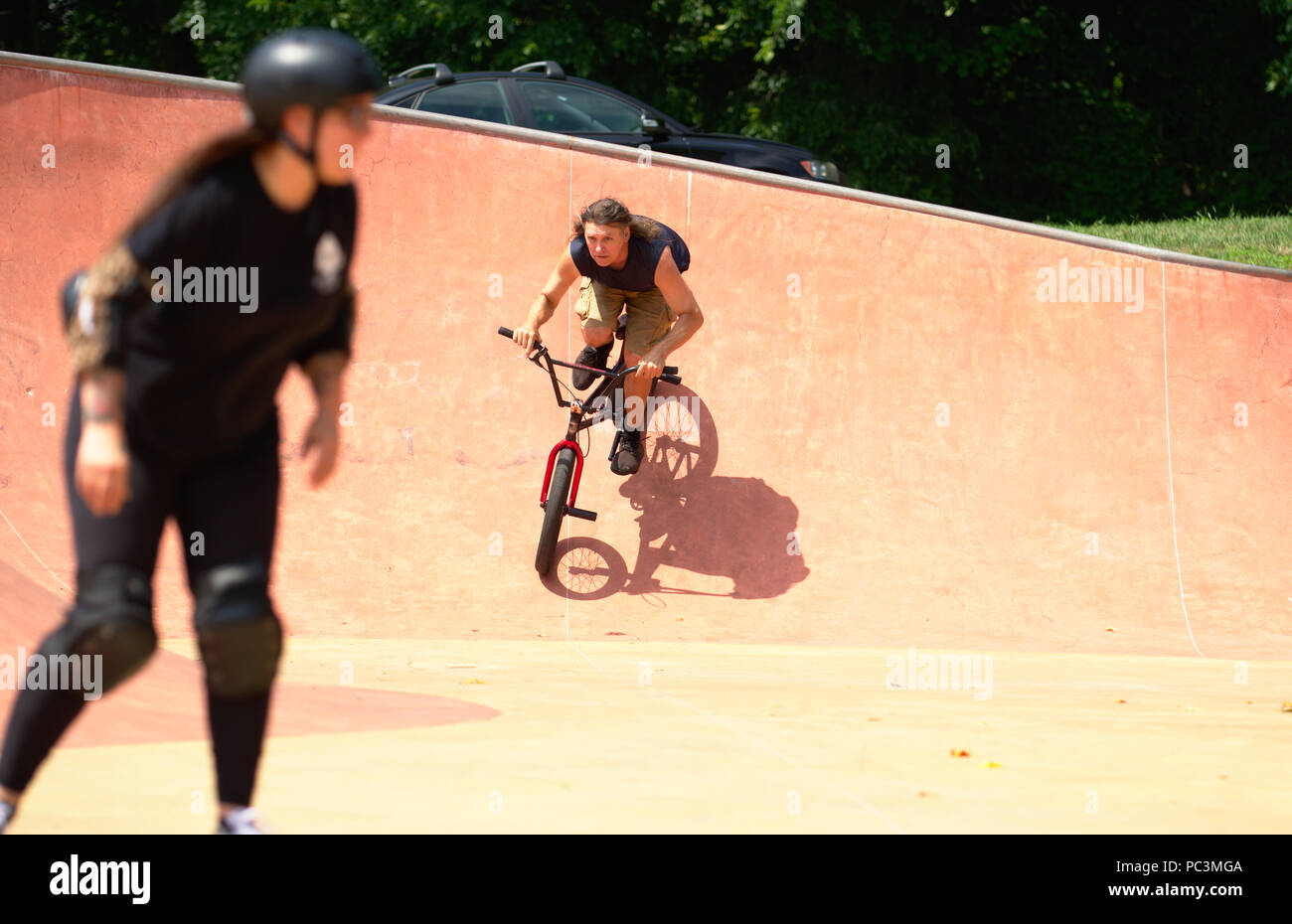 Adult male on BMX bike at park with female skateboarder in ...