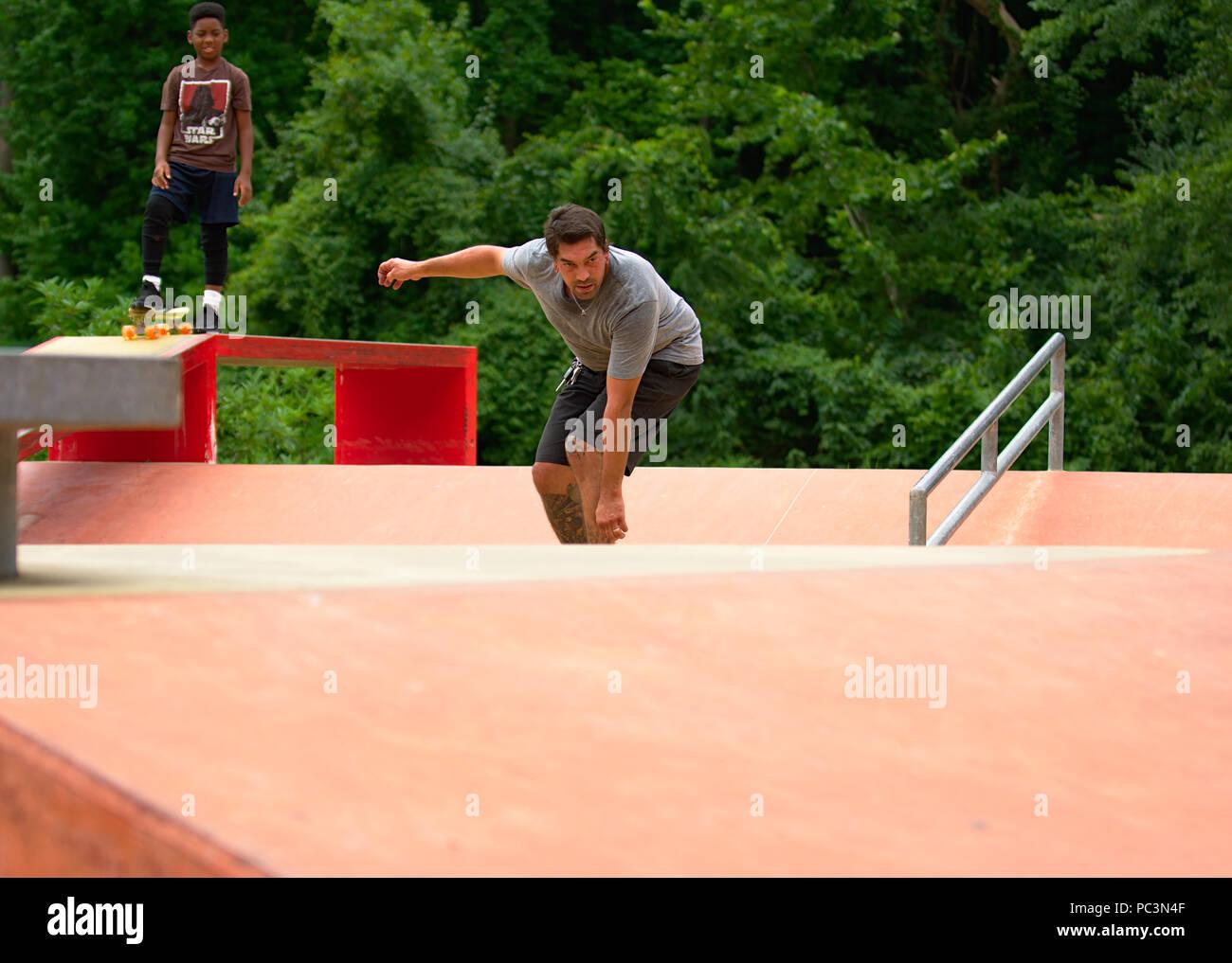 Pre Teen watching 30+ adult skateboarding - Stock Image
