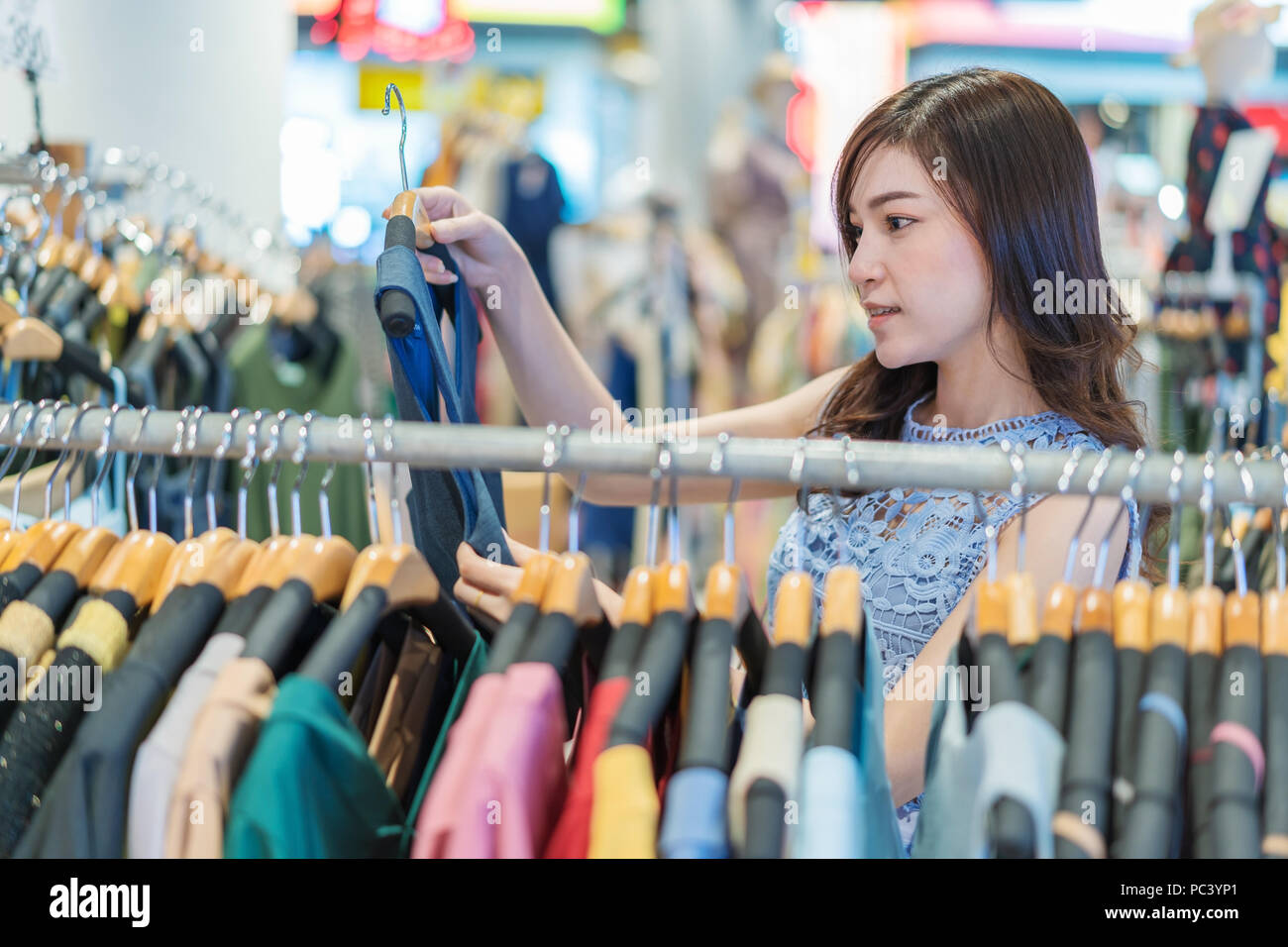 154cf075be80c young woman shopping in a clothing store Stock Photo: 213987929 - Alamy