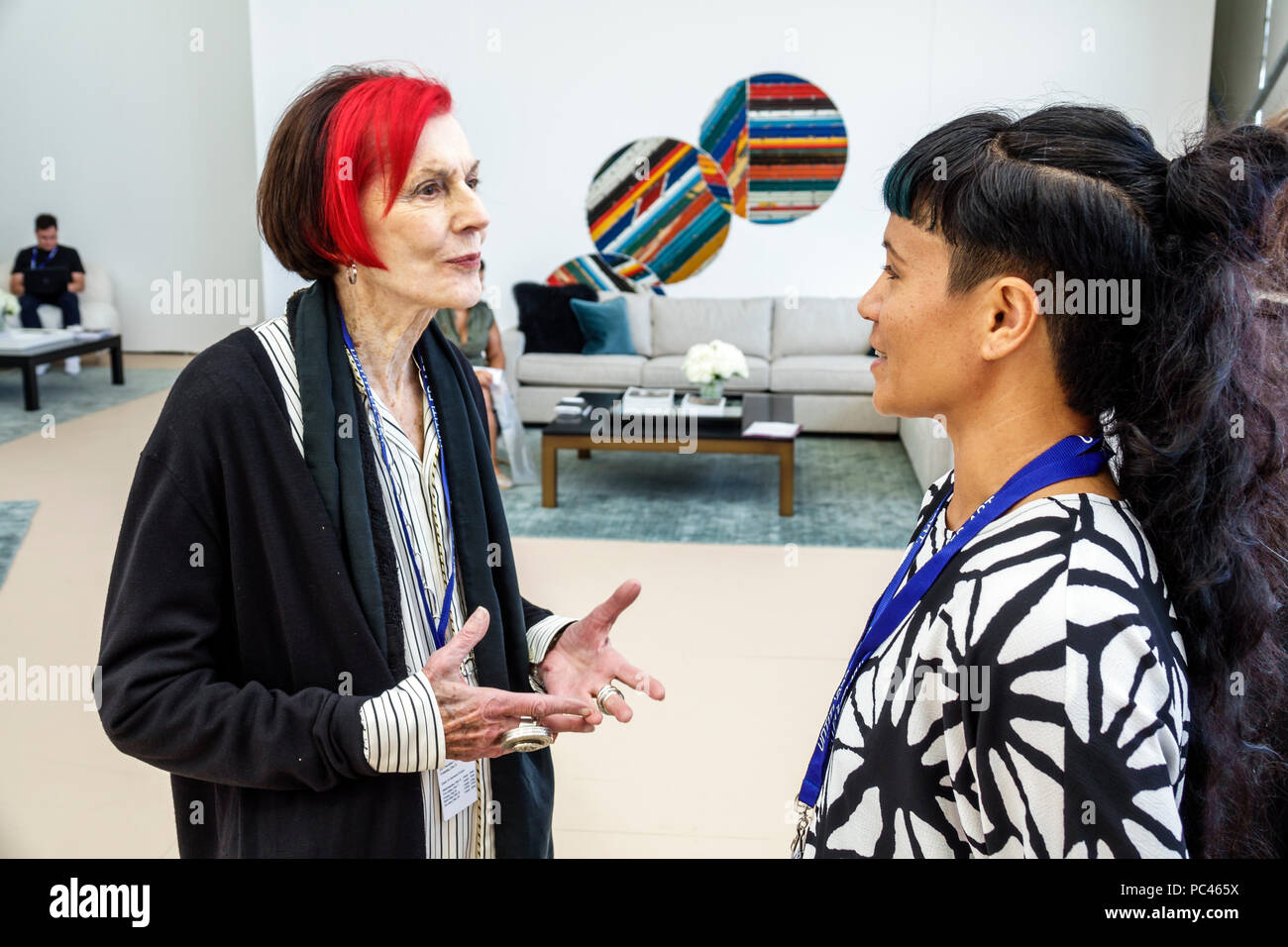 Miami Beach Florida Art Basel Week Untitled gallery show event contemporary woman mature trendy haircut bright red hair coloring talking hands gesturi - Stock Image