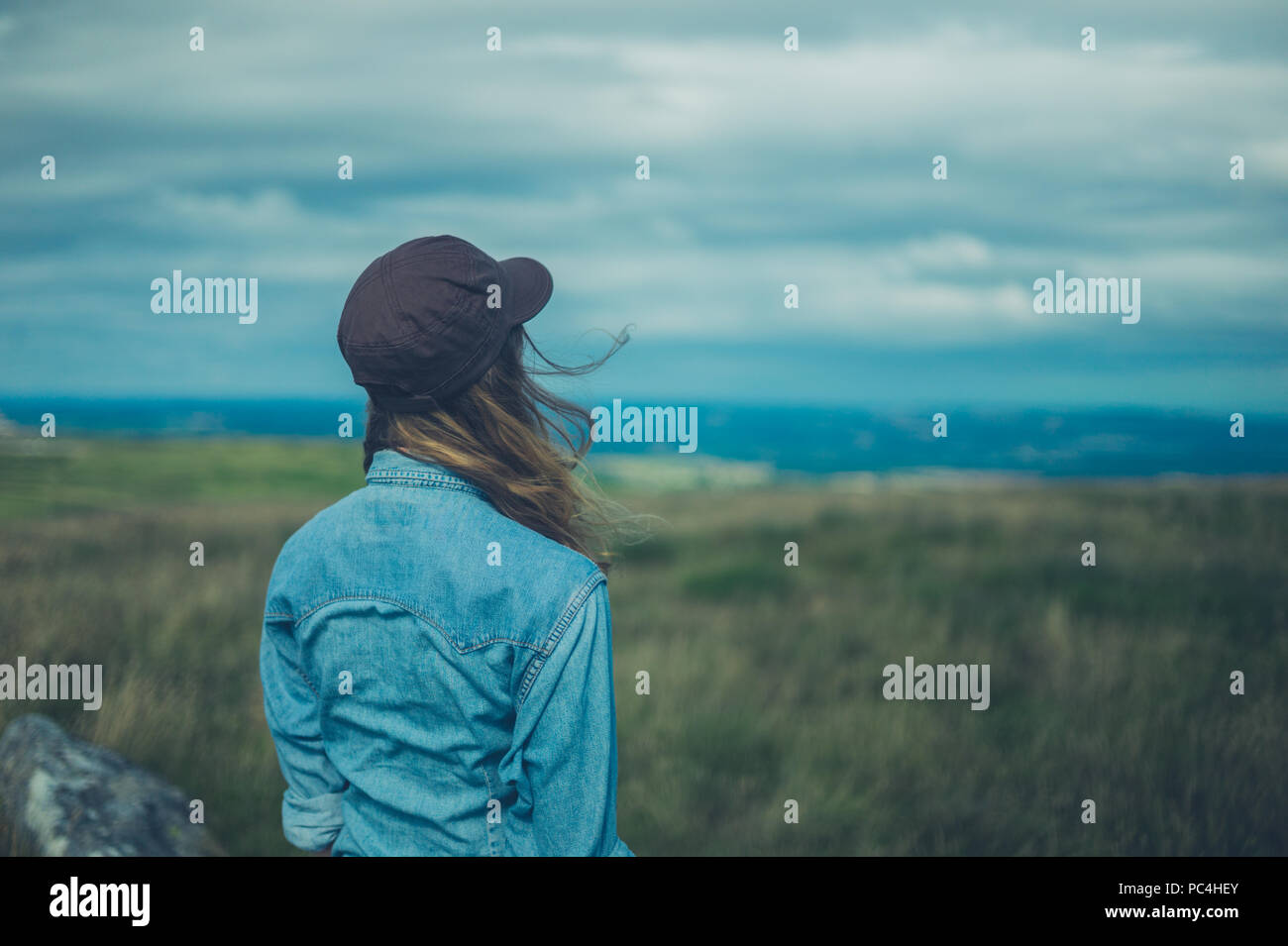 A young woman wearing a baseball cap is standing on a hilltop - Stock Image