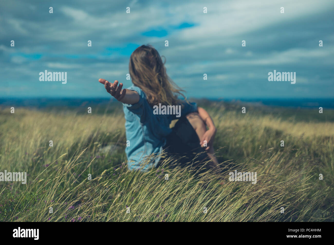 A young woman sitting in a field is offering a hand - Stock Image