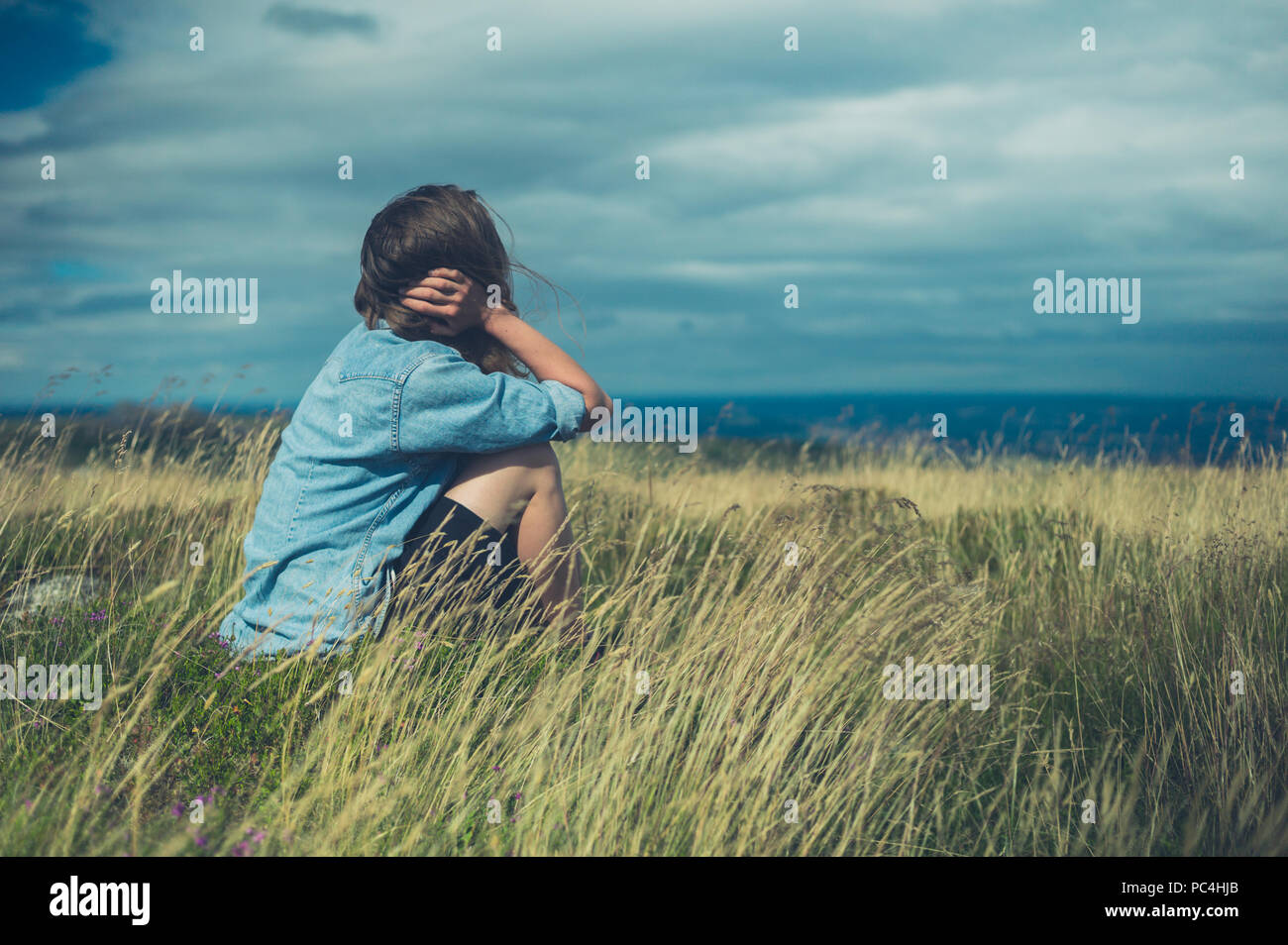 A sad woman is sitting in a field on a windy day - Stock Image