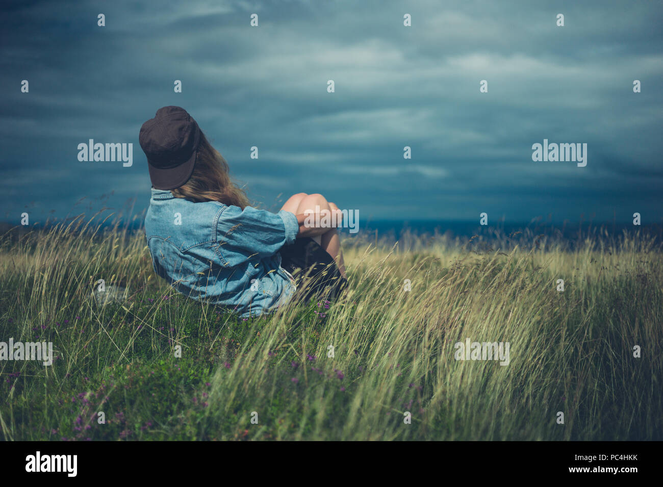 A young woman is sitting in a field on a windy day - Stock Image