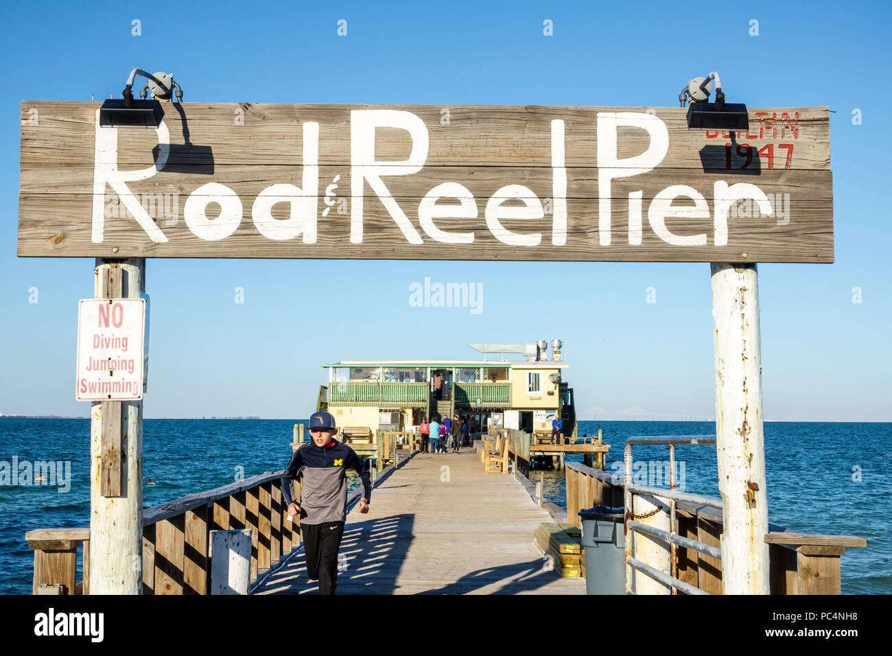 Florida Anna Maria Island Anna Maria City Pier Rod & Reel restaurant wood fishing pier rustic sign boy teen walking - Stock Image
