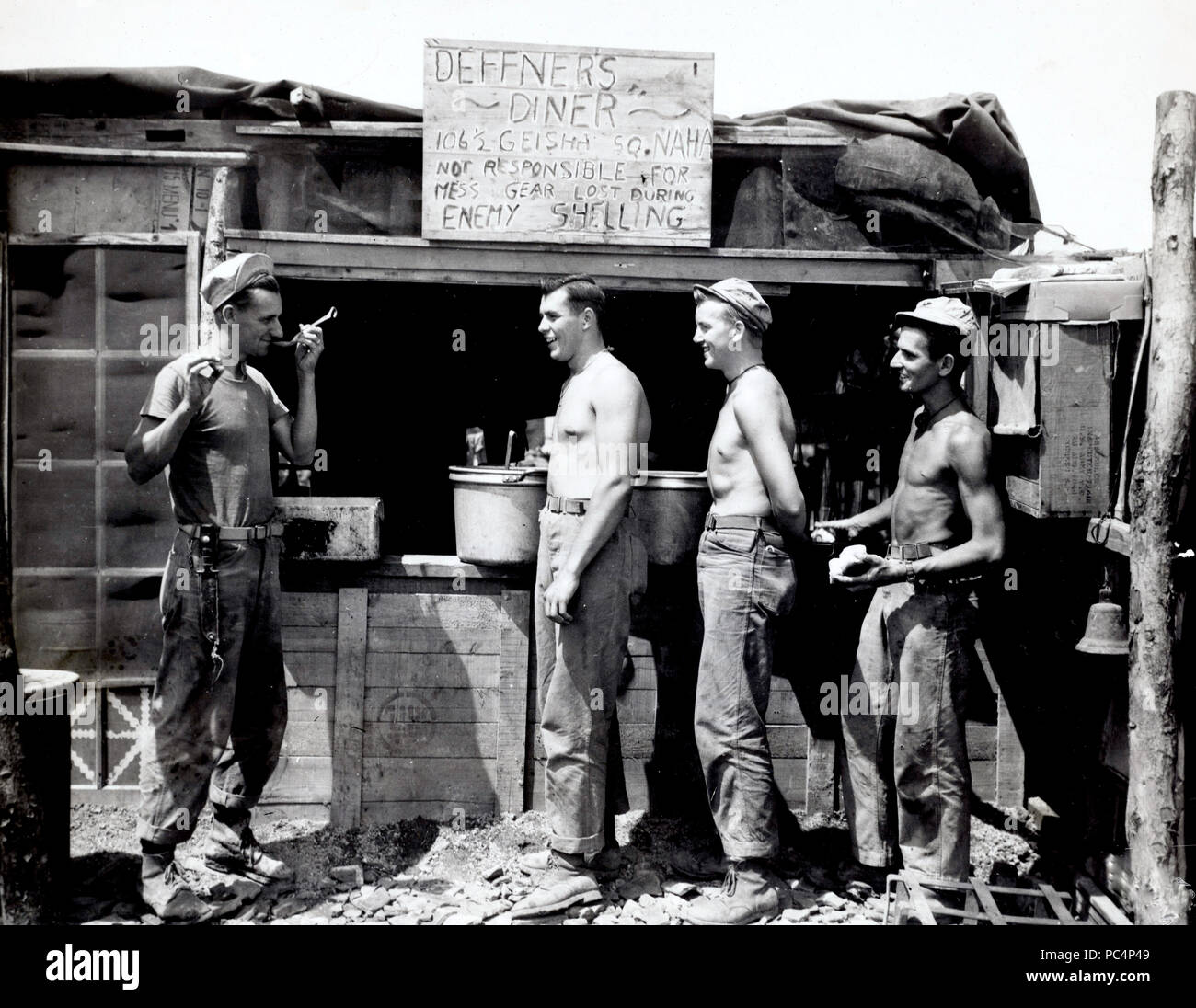Mess Sgt Corporal Nelson Deffner tastes his own chow and shows his sense of humor with a sign at mess hall on Okinawa - Stock Image