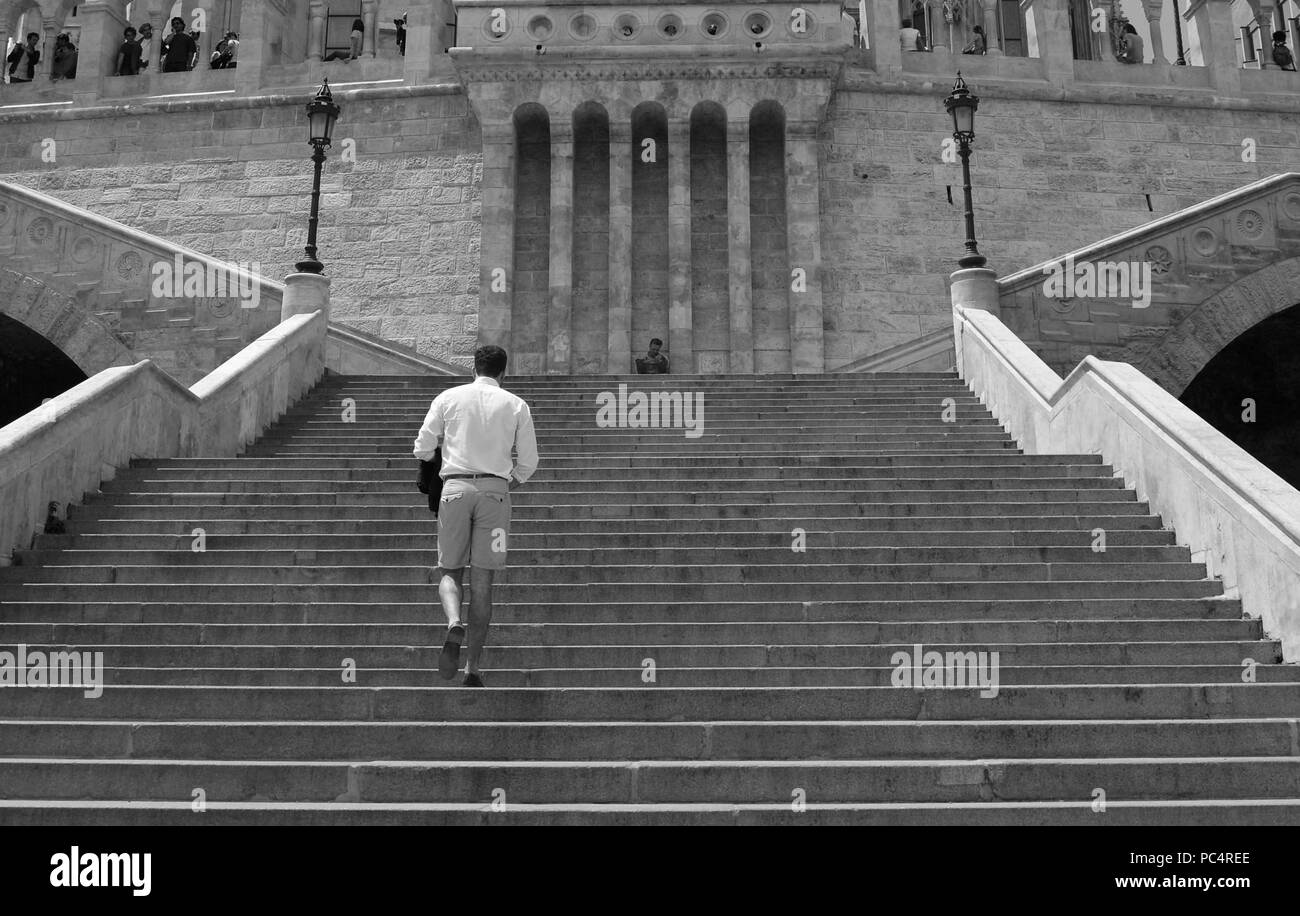 Man walking up the stairs of Fishermen's Bastion in Budapest while a man is painting in the background - Stock Image