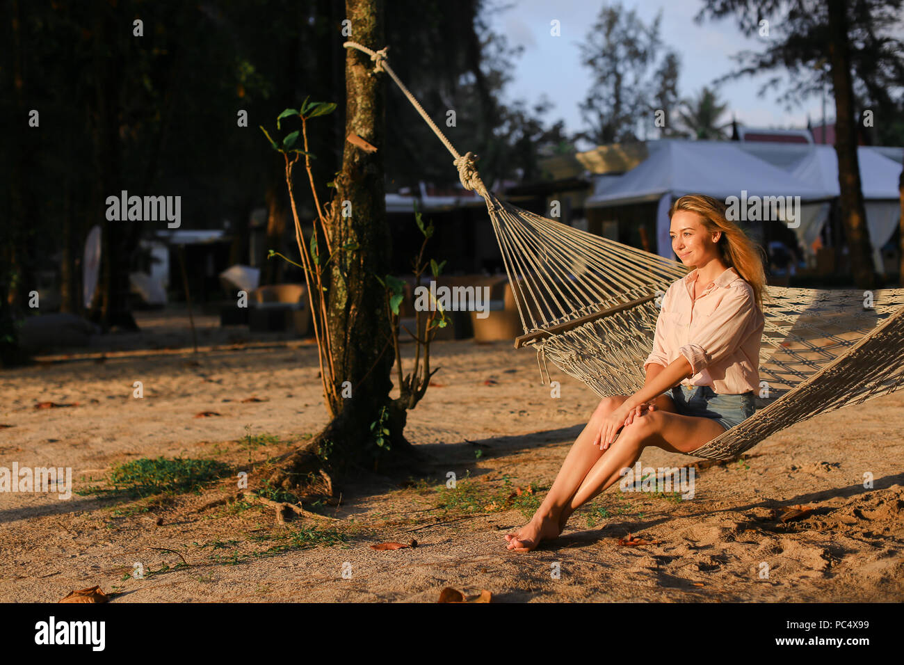 Young caucasian barefoot woman resting on sand in white wicker hammock. - Stock Image