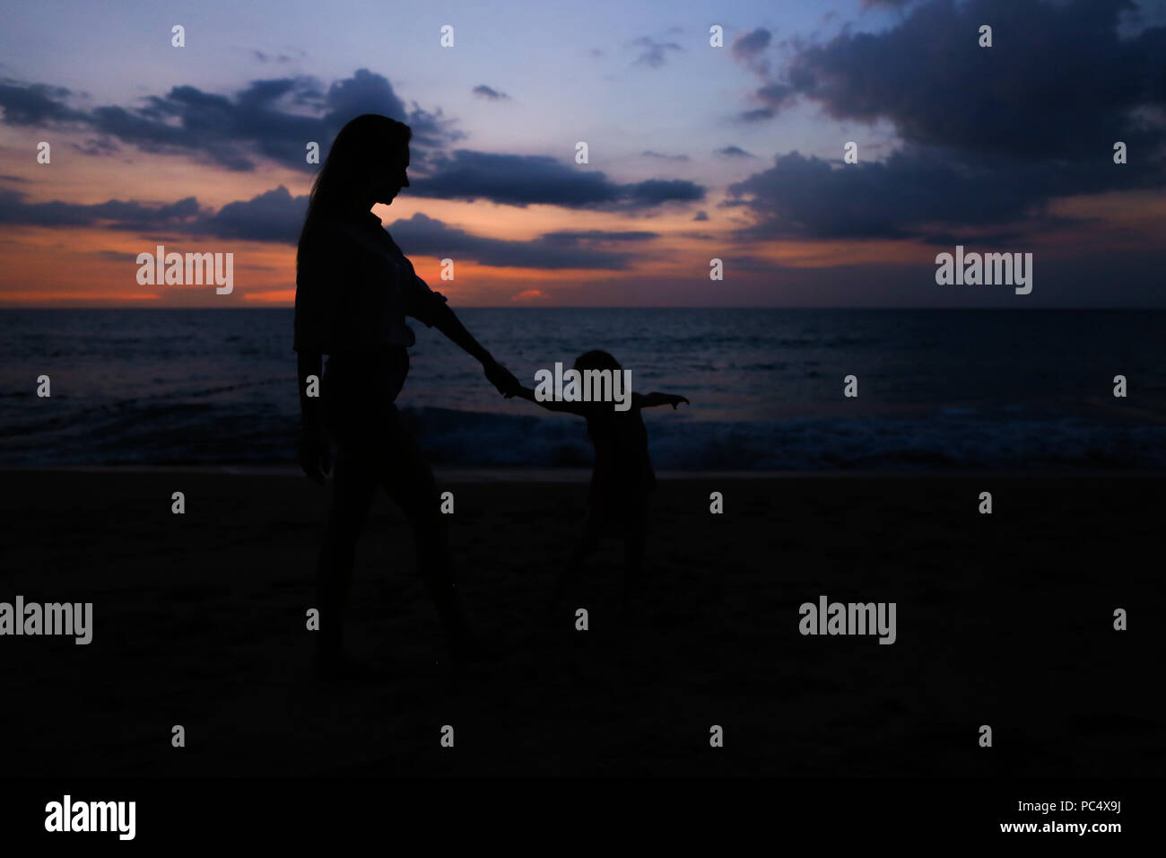 e4cf926558ef Silhouette of young mother walking with little daughter near sea in sunset.  - Stock Image