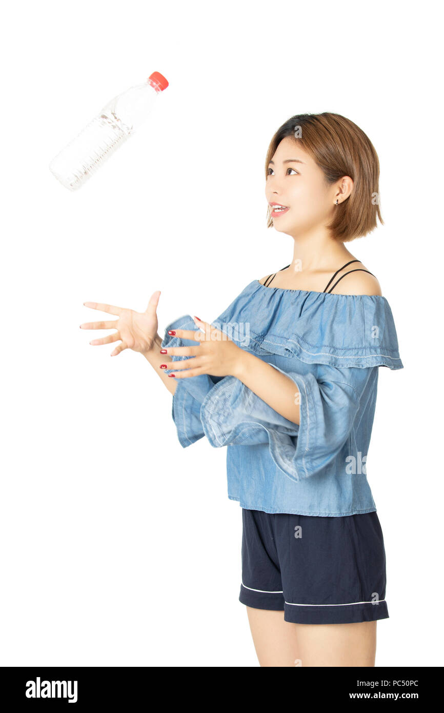 Portrait of happy beautiful Chinese woman holding water bottle isolated on a white background - Stock Image