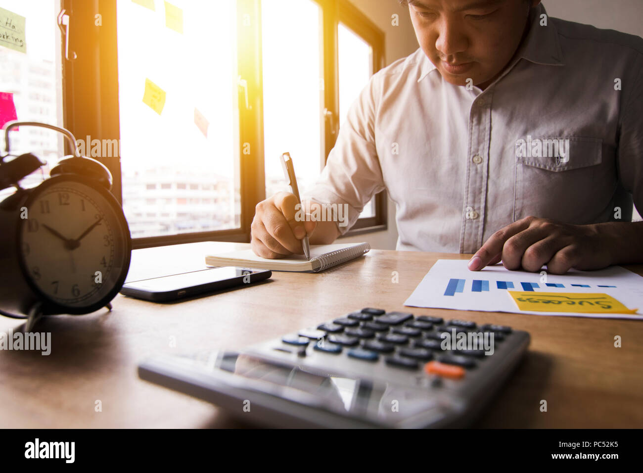 Accountant calculate finance of annual profit by press calculator and summed up balance money by writing on note book in office - Stock Image