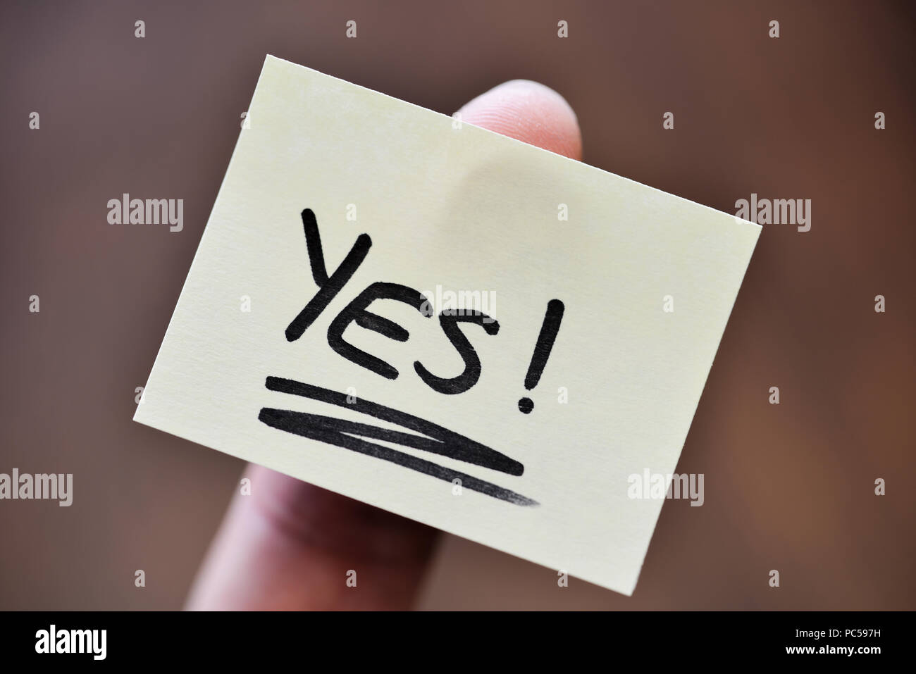 Success / Goal Concept - Index Finger Holding Note With Handwritten YES Word - Stock Image