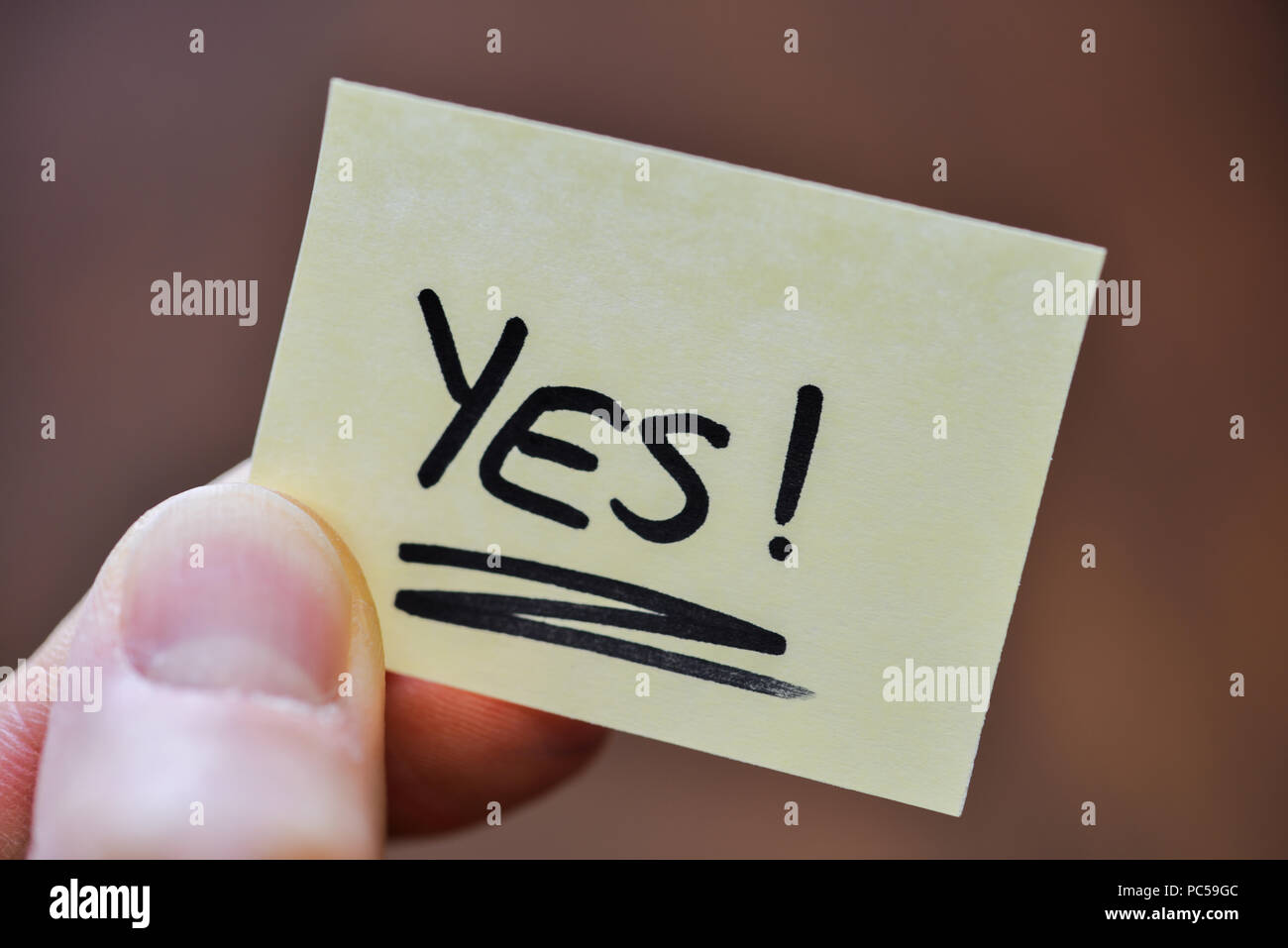 Success / Goal Concept - Fingers Holding Note With Handwritten YES Word - Stock Image