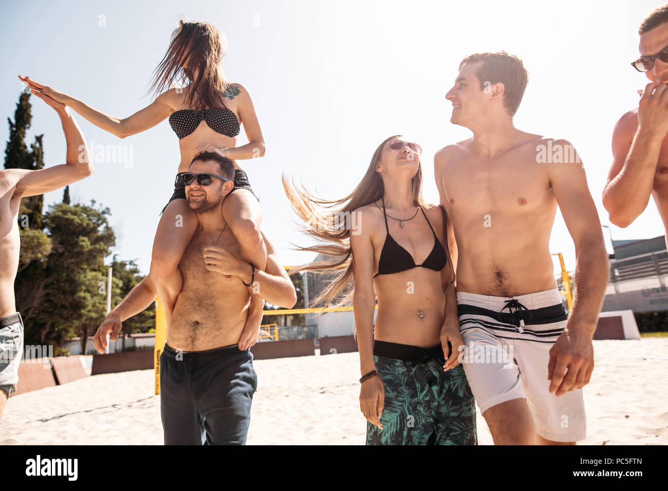 European adult people, cheerful guys and girl, spending their leisure time on hotel sandy volleyball field, having fun, living healthy active lifestyl - Stock Image