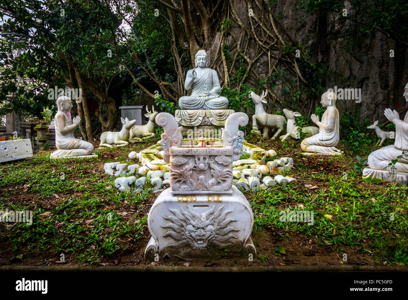 A group of animals and other Buddha's in a forest sourronding a bigger Buddha. - Stock Image