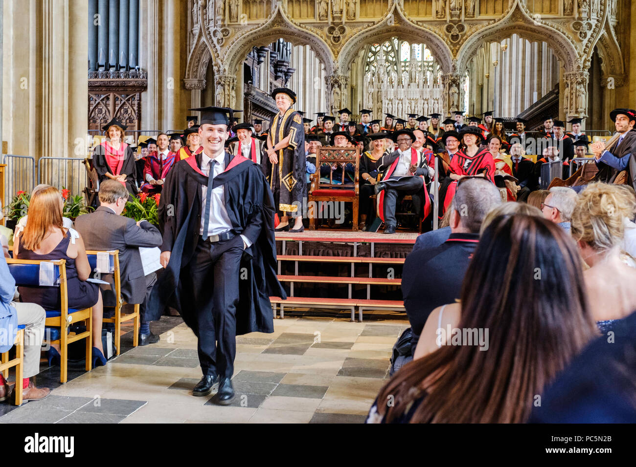 New graduate, young man aged 21, smiling while walking down aisle after graduating. Academic congregation sitting on platform and smiling. - Stock Image