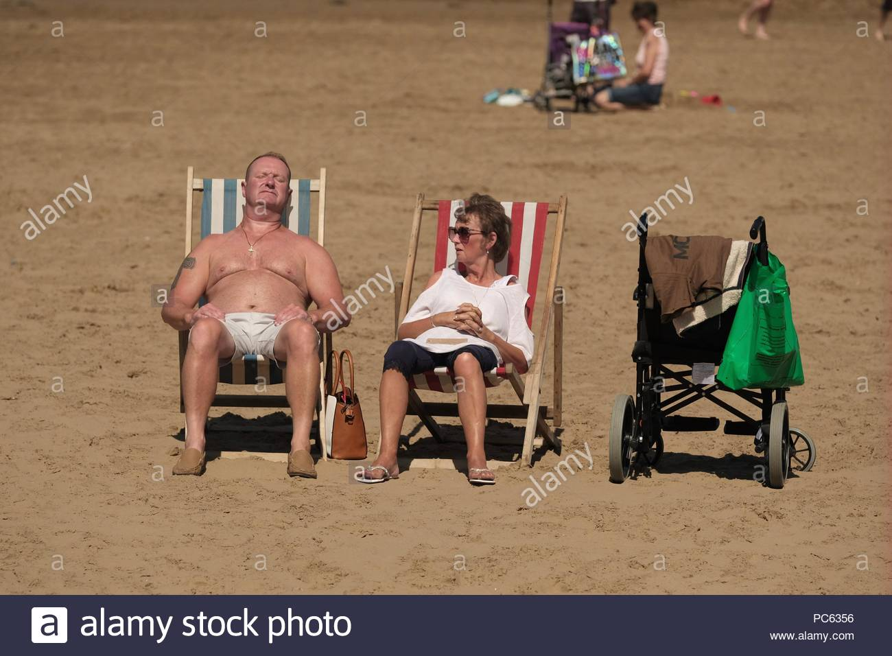 An elderly couple relax in deckchairs on the beach at weston-super-mare, UK. The warm weather was a feature of the 2018 summer with the heatwave continuing through july into august - Stock Image
