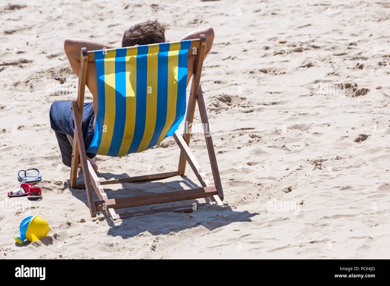 Bournemouth, Dorset, UK. 31st July 2018. UK weather:  the sun returns and temperatures rise as beach-goers head to the seaside to enjoy the warm sunny weather. man relaxing in deckchair on the beach. Credit: Carolyn Jenkins/Alamy Live News - Stock Image
