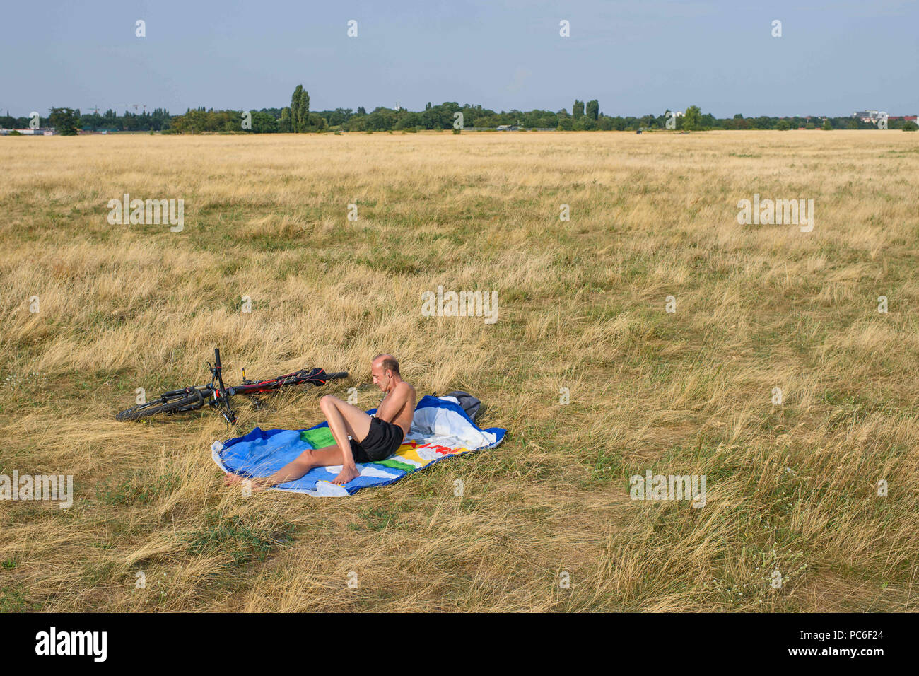 Berlin, Germany. 01st Aug, 2018. A Berlin citizen lies alone on a dry meadow on the Tempelhofer Feld on a warm summer day. Credit: Gregor Fischer/dpa/Alamy Live News - Stock Image