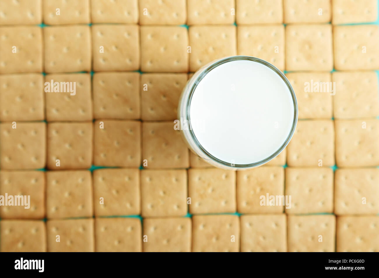 lots of crackers, appetizing background. square crackers are laid out in rows,  on the crackers there is a glass with milk - Stock Image
